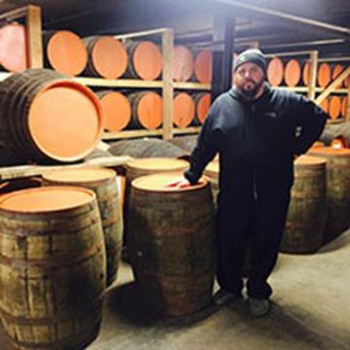 Against the Grain owning partner Sam Cruz picks up his empty brandy barrels at Copper & Kings to begin the aging process for a custom craft beer to serve at Lock, Stock & Smoking Barrels Oct. 30, 2015.