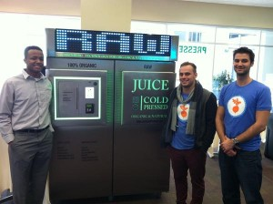 The Juice Cold Pressed team next to their creation. Don't you dare question the rawness.